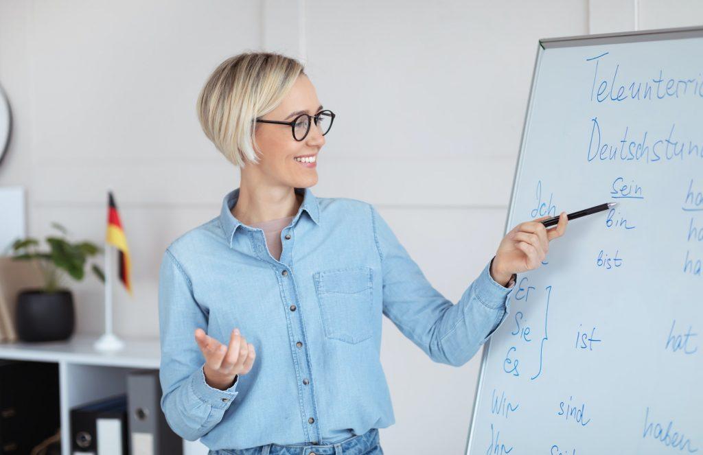 Positive German teacher explaining foreign language rules near blackboard indoors, panorama