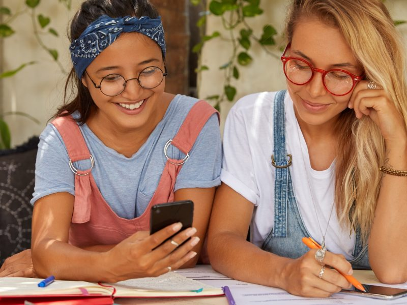 Photo of sisters or coworkers use cellular, give each other advice, translate article, write records